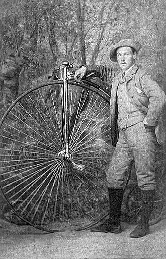 Penny-farthing - Man standing next to a penny farthing in Fife, Scotland, 1880