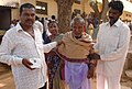 A visually challenged old man voter is being taken towards the polling station for voting at a polling booth of South Bangalore during General Elections-2008 of the Legislative Assembly of Karnataka, on May 10, 2008.jpg