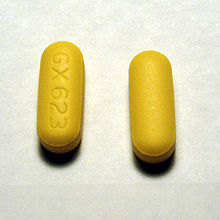 Two yellow oblong pills on one of which the markings GX623 are visible