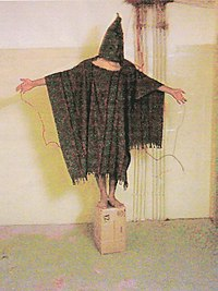 Satar Jabar standing on a box with wires connected to his body