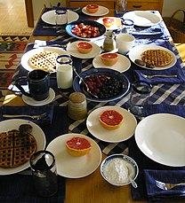 Table covered in mugs, glasses of milk, and plates of waffles, berries, powdered sugar, and grapefruit.