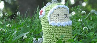 Amigurumi - Amigurumi llama in a dinosaur costume in a field