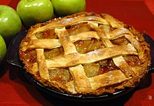 An apple pie on a red tablecloth, with green apples next to it.