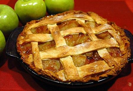 فطيرة تفاح على غطاء طاولة أحمر، وبجانبها تفاحات خضراء.