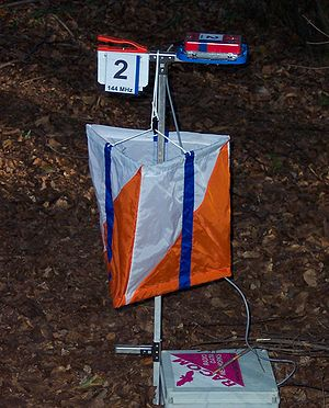 Amateur radio direction finding - A transmitter, orienteering control flag, paper punch and electronic punch device at an ARDF control.