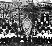 Photo en noir et blanc d'une équipe de football posant autour de son blason et de ses trophées au centre.