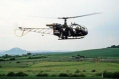 """Groen geschilderde helikopter met """"Bundesgrenzschutz"""" aan de zijkant vliegt parallel aan een grenshek met een poort erin, waarachter twee Oost-Duitse soldaten en een vrachtwagen met canvas zijkanten staan."""