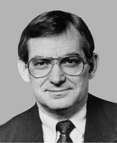 A dark-haired man in his fifties, wearing glasses and a suit, facing straight ahead