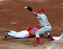Thome with an outstretched glove about to catch a pickoff throw to first base; meanwhile, Terrmel Sledge dives back safely.