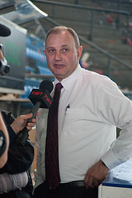 Brent Sutter wearing a white button down shirt and red tie with an interviewer holding a microphone in front of him