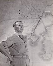 Black and white photo of a middle-aged man wearing military uniform pointing a stick at a map of the Tokyo region of Japan
