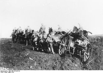 Operation Michael - Soldiers help man-handle horse-drawn German 77mm field gun forward over shell-torn ground, March 1918