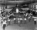 Carlisle Students in School Uniform Exercising Inside Gymnasium; Some with Indian Clubs, Others with Gymnastic Equipment; Non-Native Group Watching 1879.jpg