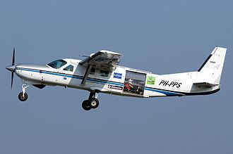Cessna 208 Caravan - 208B Grand Caravan in the Netherlands, modified with roller door for parachuting operations; skydivers sitting on the cabin floor are visible inside the rear roller door