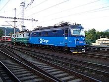 Photo couleur de deux locomotives électriques en approche d'une gare. Elles ont la même carosserie, mais la première arbore une livrée en deux teintes de bleu récente et la seconde une livrée en deux teintes de vert passablement délavée.