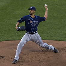 A man in gray pants, a blue baseball jersey with 'Rays' on the chest, and a blue baseball cap is in the process of pitching a baseball with his left hand.