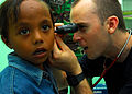 Defense.gov News Photo 100720-N-4044H-021 - U.S. Navy Lt. Timothy Chinnock a doctor assigned to the Military Sealift Command hospital ship USNS Mercy T-AH 19 examines a child s ear during.jpg