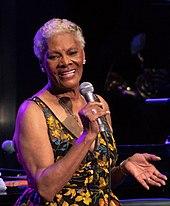 Una mujer de piel oscura y cabello gris con un vestido de estampados brillantes cantando en un micrófono