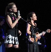 Two young women performing on a stage, one singing into a microphone and the other playing a guitar