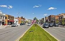 Una calle ancha con carreteras de dos carriles en cualquier dirección y edificios comerciales más antiguos a cada lado, visto desde una mediana cubierta de hierba con la bandera estadounidense ondeando desde un poste bajo en el centro.