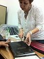 Dr. Iman, Professor at Ain Shams, holding a book in Arabic with her students' research.jpg