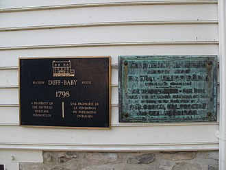 "Duff Baby House - Duff-Baby House historical plaques. The right plaque reads ""This dwelling was erected about 1790 by Hon. James Baby, legislative councillor. The headquarters of Gen. Hull when he invaded Canada in 1812, subsequently occupied by Gen. Brock, Col. Proctor and Gen. Harrison."""