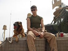 A black and tan German Shepherd dog sits next to a Marine atop a HECO barrier with a MTVR in the background. Lex is holding a red Kong toy in his mouth while Lee is wearing sunglasses and fire-resistant coveralls open to his waist.