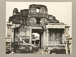 Ruins of a temple, entirely made of stone. The four-storied temple ruins rise behind two free-standing pillared structures, one of which hides the entrance to the temple. Sculptures of human forms are seen on the upper stories. Grass grows on various exposed surfaces of the ruins. A pathway, paved with stone slabs, fringes the visible perimeter of the temple.