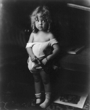 Little girl, with sunsuit slipping off her sho...