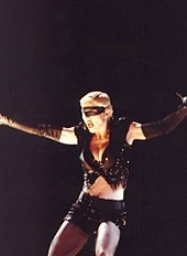 Madonna wearing black shorts and looking to her right. Her arms are open and a headset microphone to her mouth.[16]