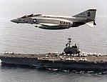 F-4J Phantom II of VF-74 in flight over USS Forrestal (CV-59), in 1981 (NNAM.1996.253.7268.022).jpg