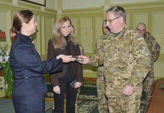 Elissa Slotkin, the acting assistant Secretary of Defense for ISA (left), presents a gift to Lt. Gen. Paulo Tkachuk, National Army Academy commander (right) in November 2015