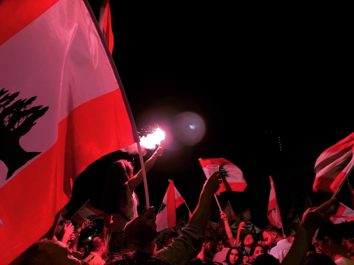 Flare shines light in group of passionate Lebanese protesters.jpg