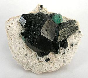 Tourmaline - A single stark green fluorite isolated on top of schorl crystals
