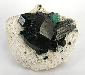 Tourmaline - A single stark green fluorite isolated on top of schorl crystals