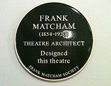 "A dark green, circular plaque with the words ""Frank Matcham (1854-1920) Theatre Architect Designed this theatre The Frank Matcham Society"" in gold lettering."