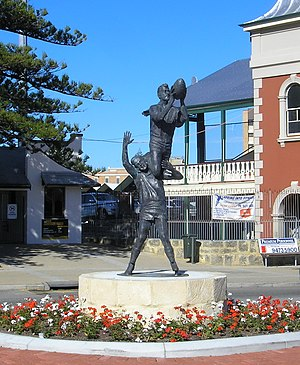"Australian rules football in Western Australia - Statue by Robert Hitchcock outside the gates Fremantle Oval of the famous ""specky"" by South Fremantle Football Club's John Gerovich over East Fremantle Football Club's Ray French at the 1956 WANFL preliminary final."