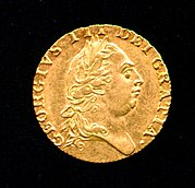 Gold coin bearing the profile of a round-headed man wearing a classical Roman-style haircut and laurel-wreath.