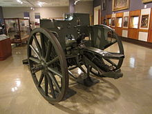 Colour photo of a green artillery gun inside the gallery of a museum. Other exhibits are visible behind the gun.