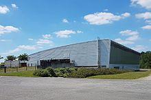 Photographie en couleurs d'un grand bâtiment moderne en métal et verre.