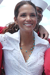 Head and shoulders shot of a smiling Berry with dark hair pulled back, wearing a lace shirt and turquoise necklace.