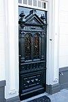 foto van Huis met dwars zadeldak tussen zij-topgevels en met gebosseerd grijsgepleisterde lijstgevel waarin ingang-omlijsting in vereenvoudigde Lodewijk xv trant