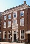 foto van De Drie Kaemeren, deftig pand met rechte kroonlijst; rijk geornementeerd rond deurpartij en vensters op beide verdiepingen er boven.