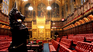 Wood-panelled room with high ceiling containing comfortable red padded benches and large gold throne.