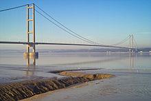 Nära bryggan i en hängbro som spänner över lugnt blått vatten i en bred flodmynning.
