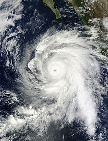 Satellite photograph of a sprawling, mature storm with a pronounced eye at the center and curving rainbands. The southern Baja California peninsula protrudes from the north.