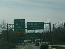 A multilane freeway in an urbanized area with two green signs over the road. The left sign reads exit 72 U.S. Route 9W Palisades Interstate Parkway Palisades Parkway Fort Lee exit upper left arrow only and the right sign reads Interstate 95 U.S. Route 1 U.S. Route 9 north George Washington Bridge