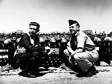 Two men crouching opposite each other, one in flying gear and the other in light-coloured uniform with forage cap