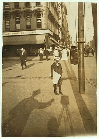 National Child Labor Committee - Lewis Hine's shadow appears in his portrait of newsboy John Howell, working the street corner in Indianapolis in 1908.