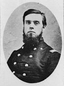 Black and white photograph shows a dark-haired young man with a beard, but no moustache. He wears a dark uniform with two rows of buttons.